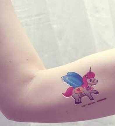 A tatuagem de uma menina na mão - um pequeno unicórnio