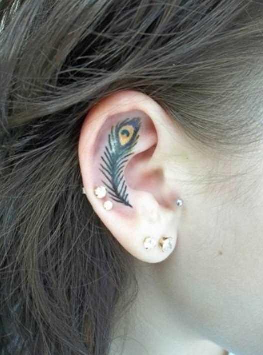 A tatuagem de uma menina na orelha - pena de pavão