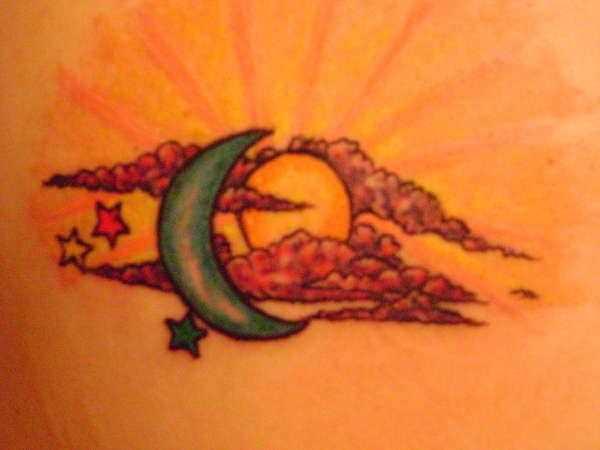 A tatuagem de uma menina na parte de trás do sol, da lua e estrelas