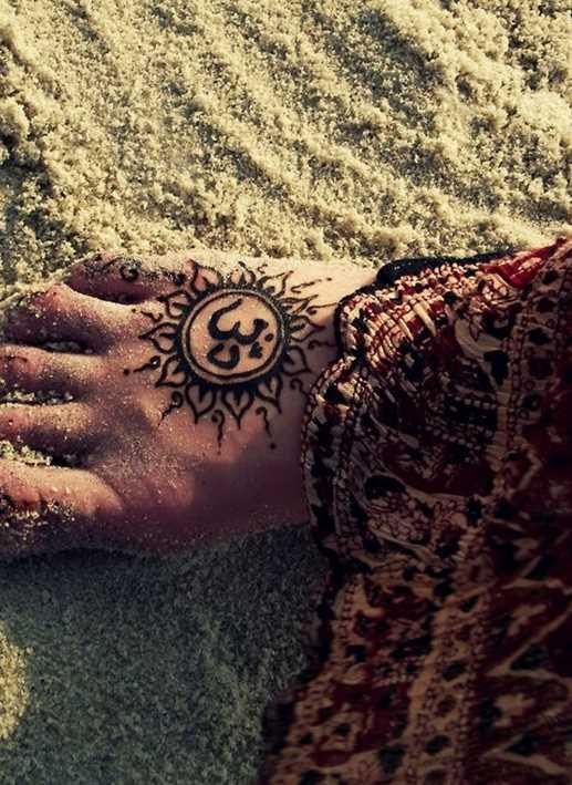 A tatuagem de uma menina na planta do pé - de- sol e um símbolo de Ohm
