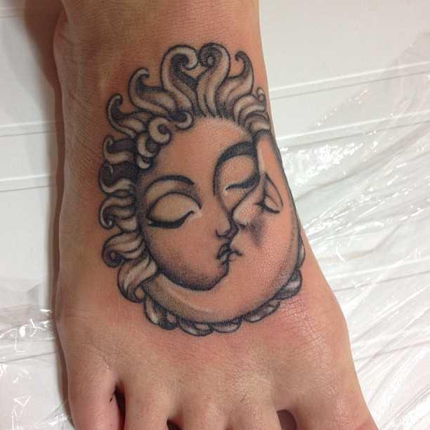 A tatuagem de uma menina na planta do pé - o sol e a lua