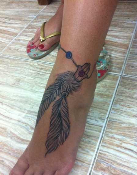 A tatuagem de uma menina na planta do pé - penas