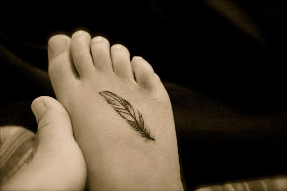 A tatuagem de uma menina na planta do pé pequeno pena