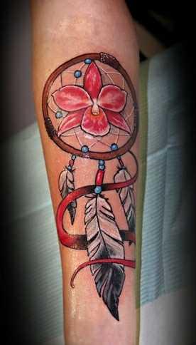 A tatuagem de uma menina no antebraço - apanhador de sonhos e orquídea