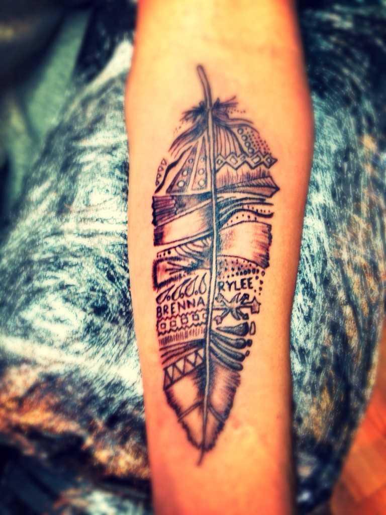 A tatuagem de uma menina no antebraço - caneta e inscrições