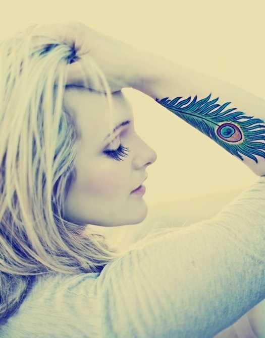 A tatuagem de uma menina no antebraço - pena de pavão