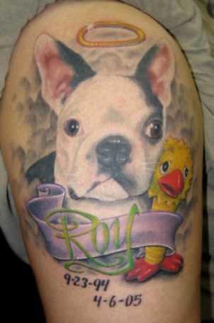 A tatuagem de uma menina no ombro - o cão e a inscrição na forma datas