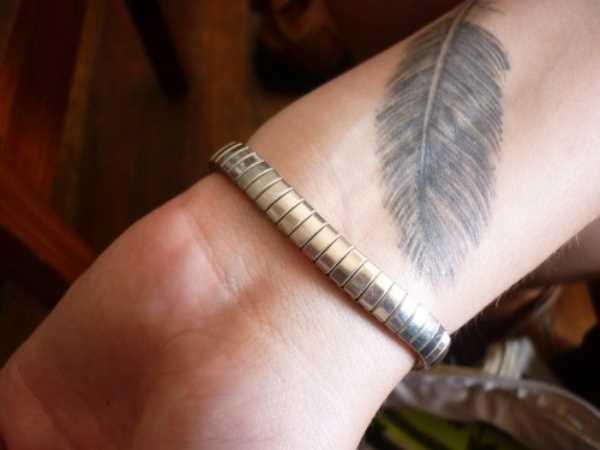 A tatuagem de uma menina no pulso em forma de plumas