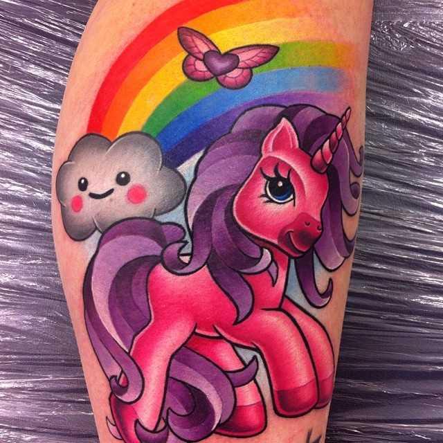 A tatuagem de uma menina sobre a perna de pequeno unicórnio e o arco-íris