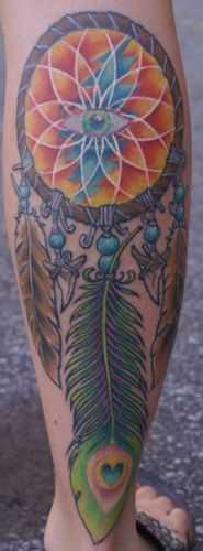 A tatuagem de uma menina sobre a perna na forma de um apanhador de sonhos