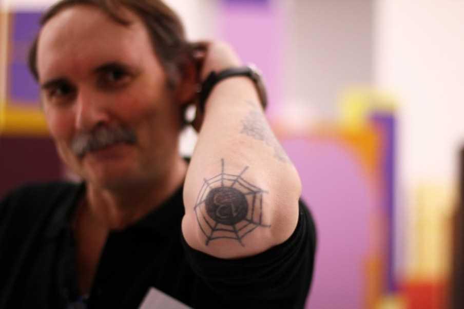A tatuagem do cara no cotovelo, na forma de web e números 13