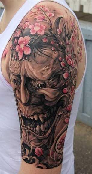A tatuagem do cara no ombro com a imagem da máscara