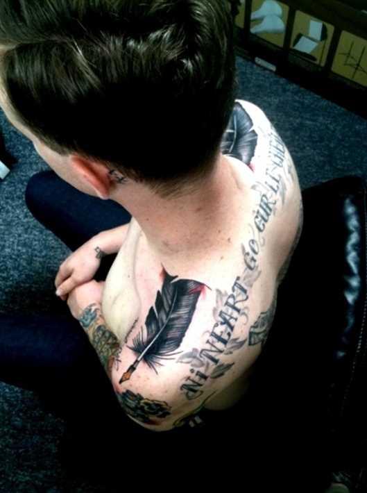 A tatuagem do cara no ombro em forma de caneta