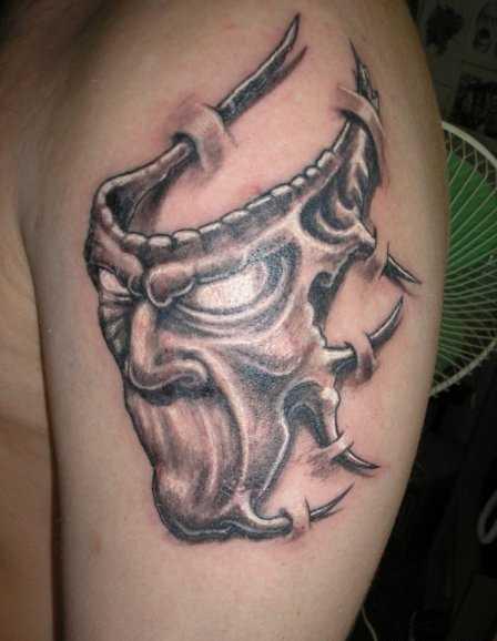 A tatuagem do cara no ombro em forma de máscara