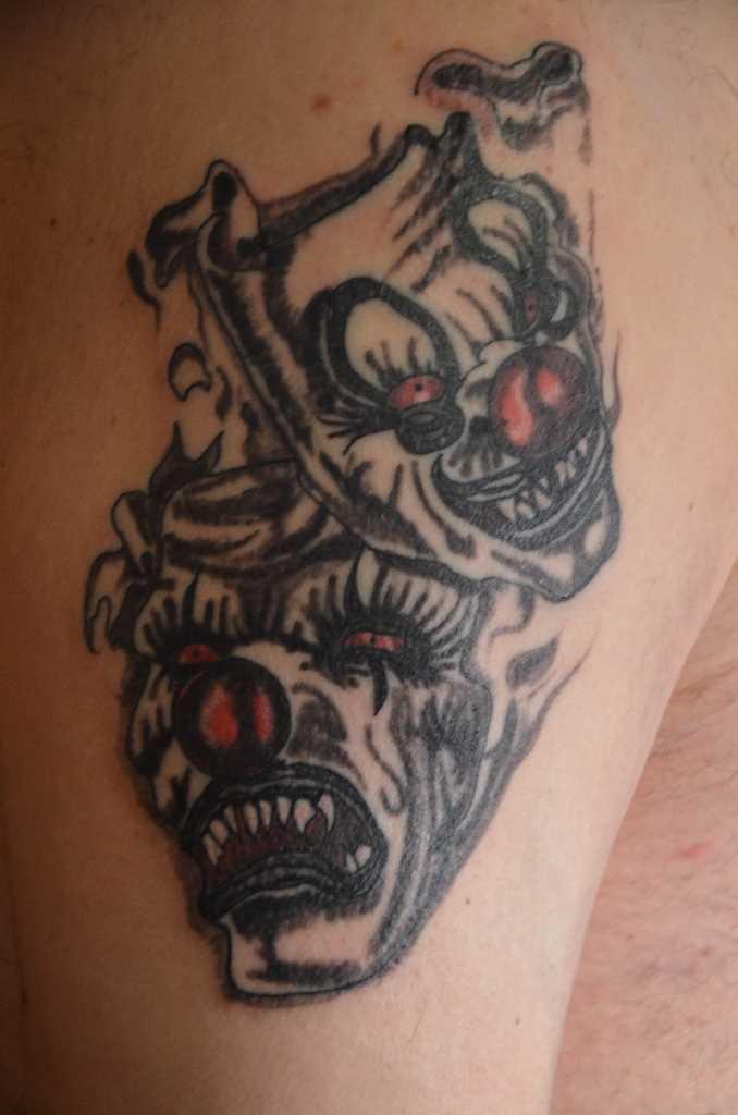 A tatuagem do cara no ombro em forma de máscaras