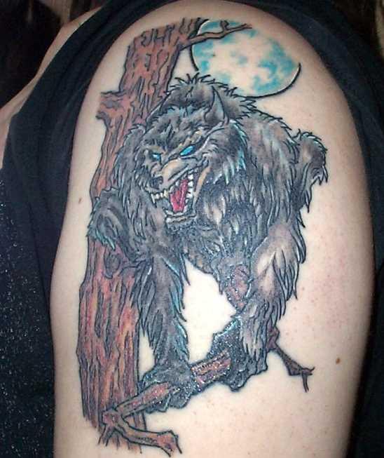 A tatuagem do cara no ombro - um lobisomem na árvore e a lua