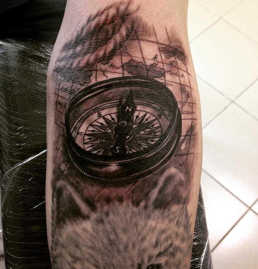 A tatuagem do compasso com o cartão no antebraço homens