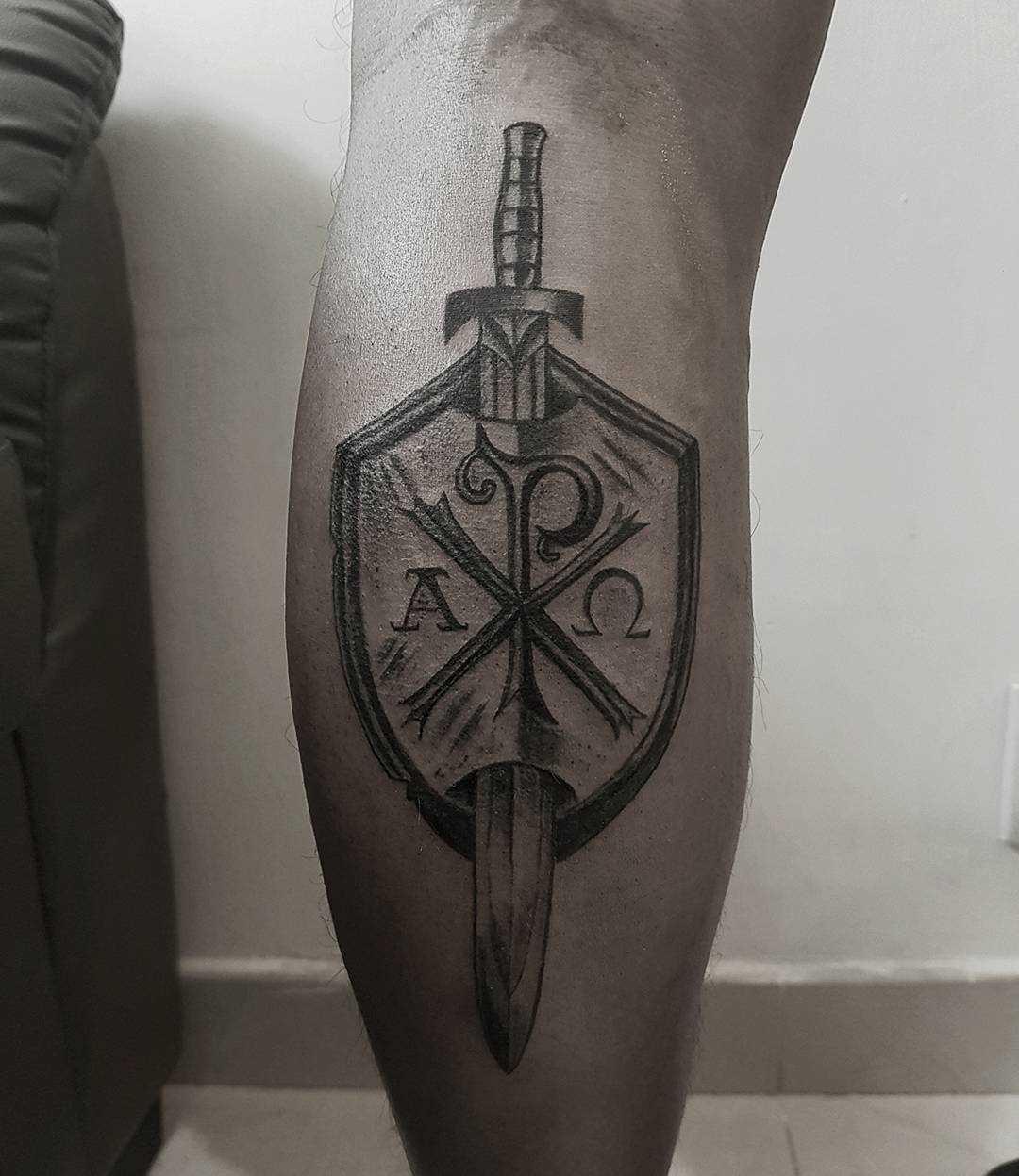 A tatuagem do escudo com a espada na perna do cara