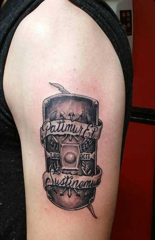 A tatuagem do escudo no ombro do cara