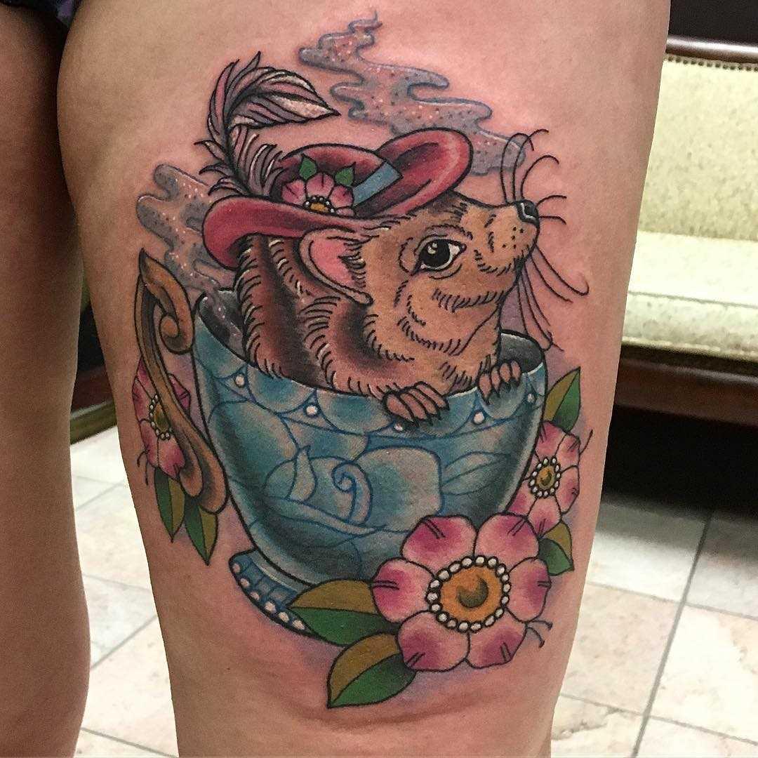 A tatuagem do ouriço em um copo no quadril da menina