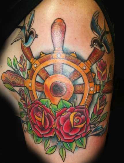 A tatuagem do volante sobre o ombro de uma mulher
