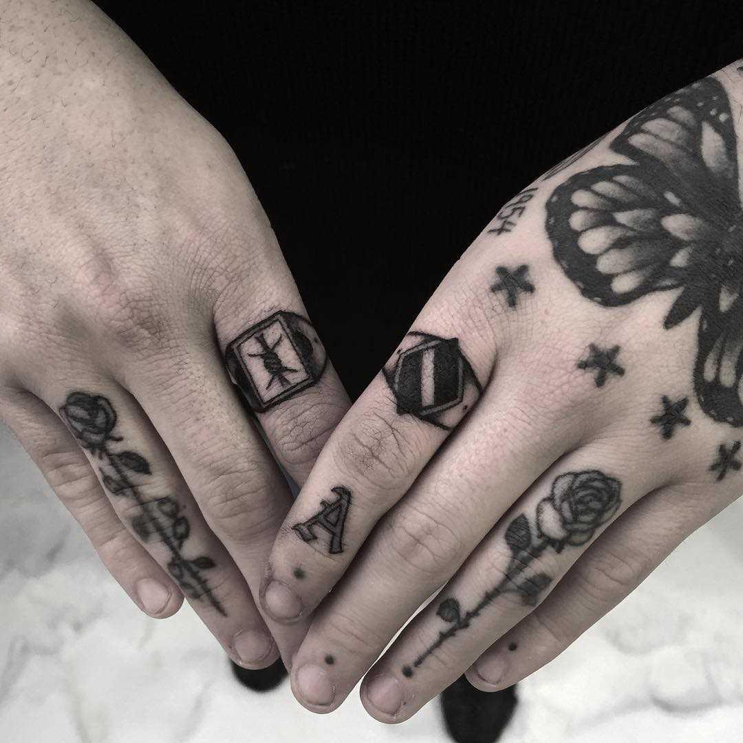 A tatuagem dos anéis em seus dedos do cara
