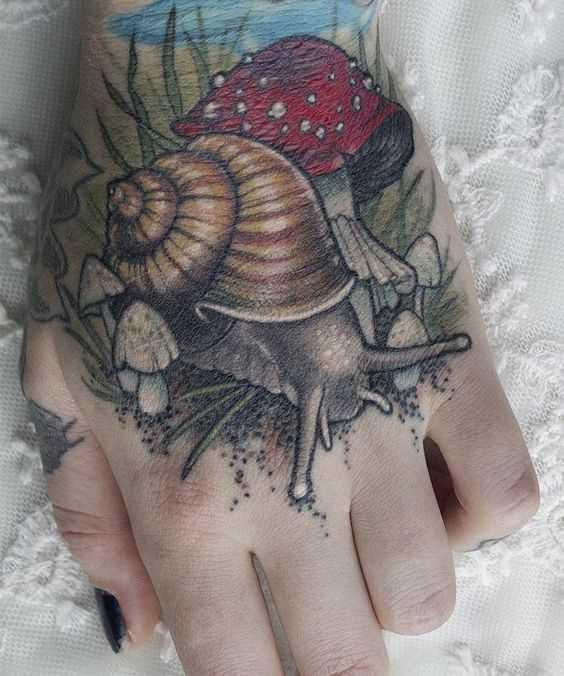 A tatuagem é um caracol com mukhomorami no pincel mulheres