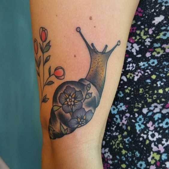 A tatuagem é um caracol na mão da mulher
