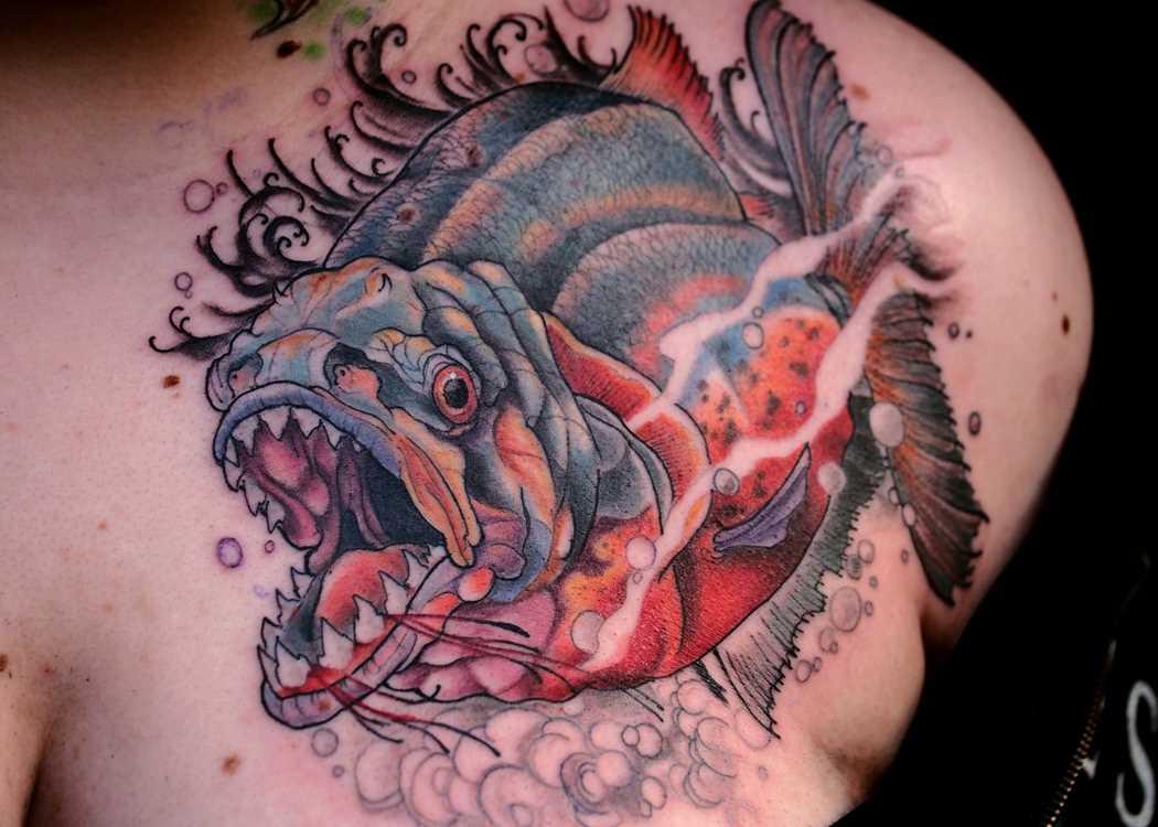 A tatuagem é uma piranha no peito de uma mulher