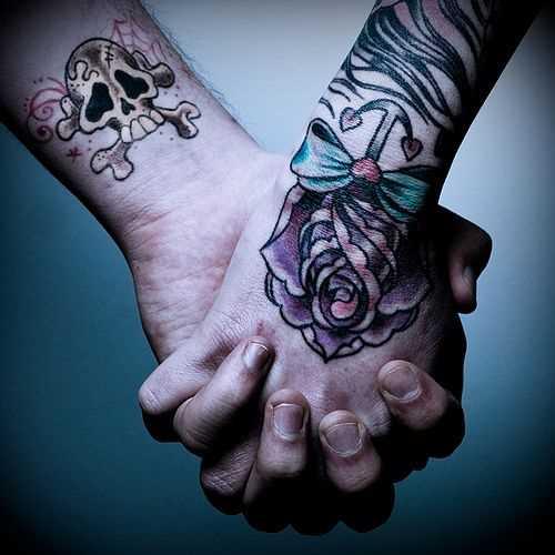 A tatuagem em forma de uma rosa com uma âncora no pincel menina