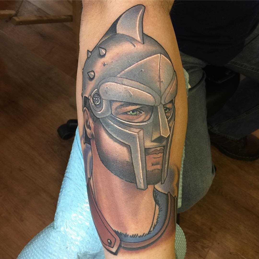 A tatuagem gladiador sobre a perna de um cara