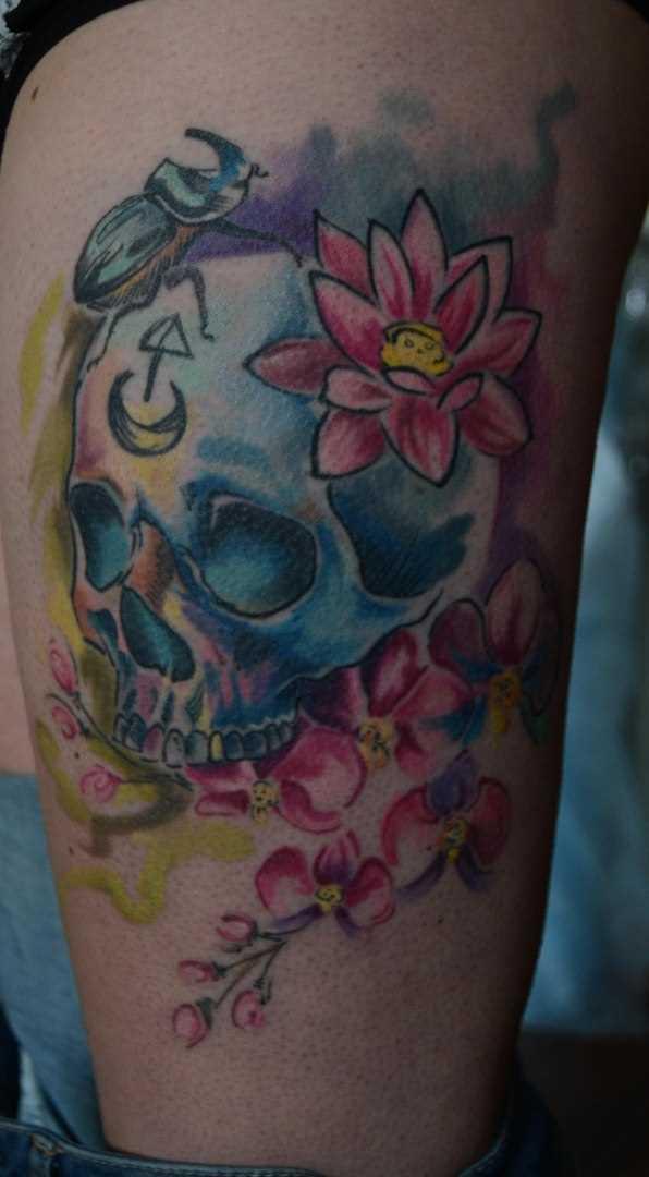 A tatuagem na sua coxa tem cara de crânio e flores