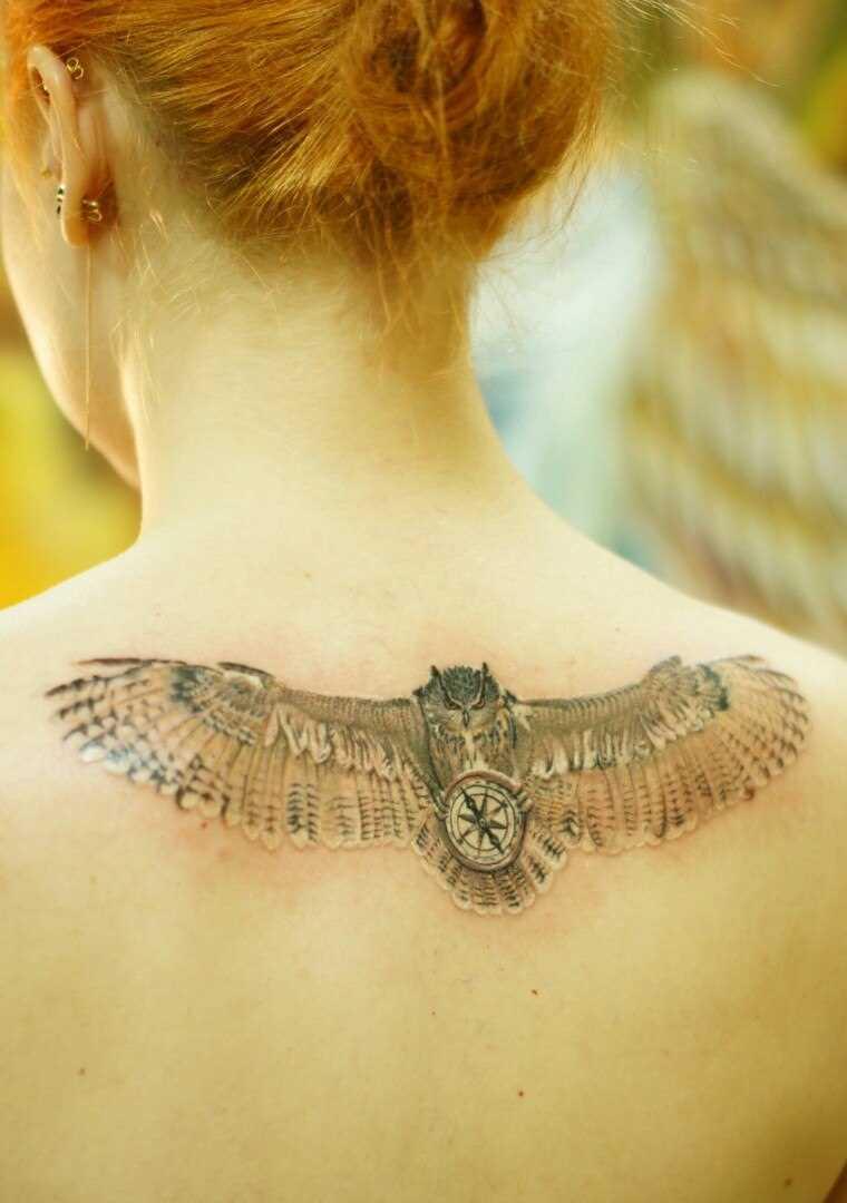A tatuagem nas costas de uma menina - coruja