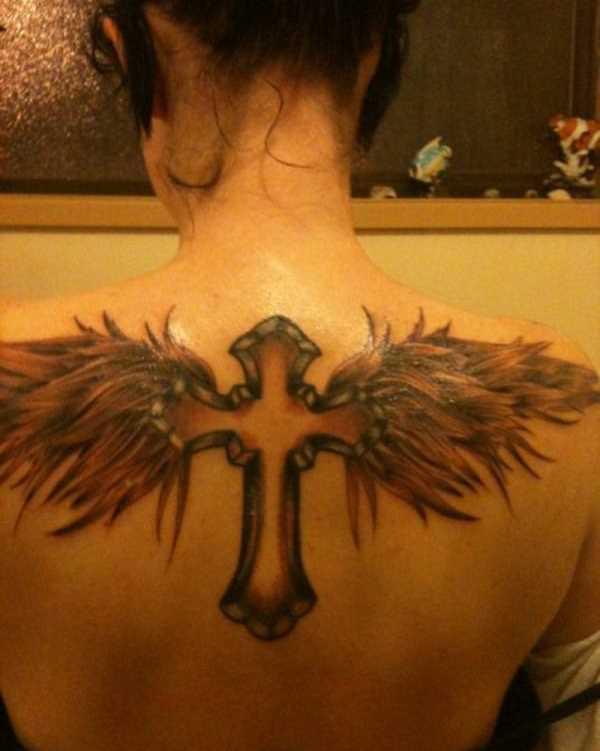 A tatuagem nas costas de uma menina - cruz com asas