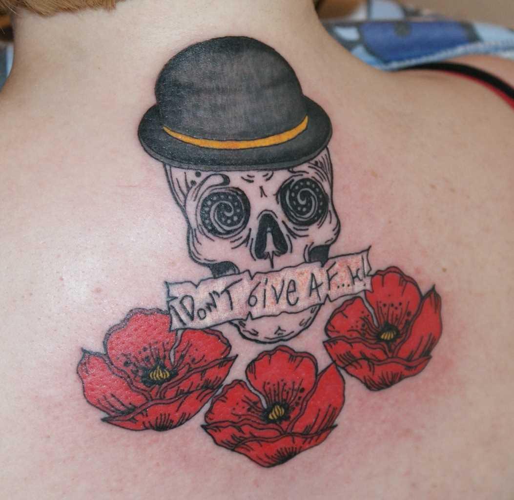 A tatuagem nas costas de uma menina de crânio e macs