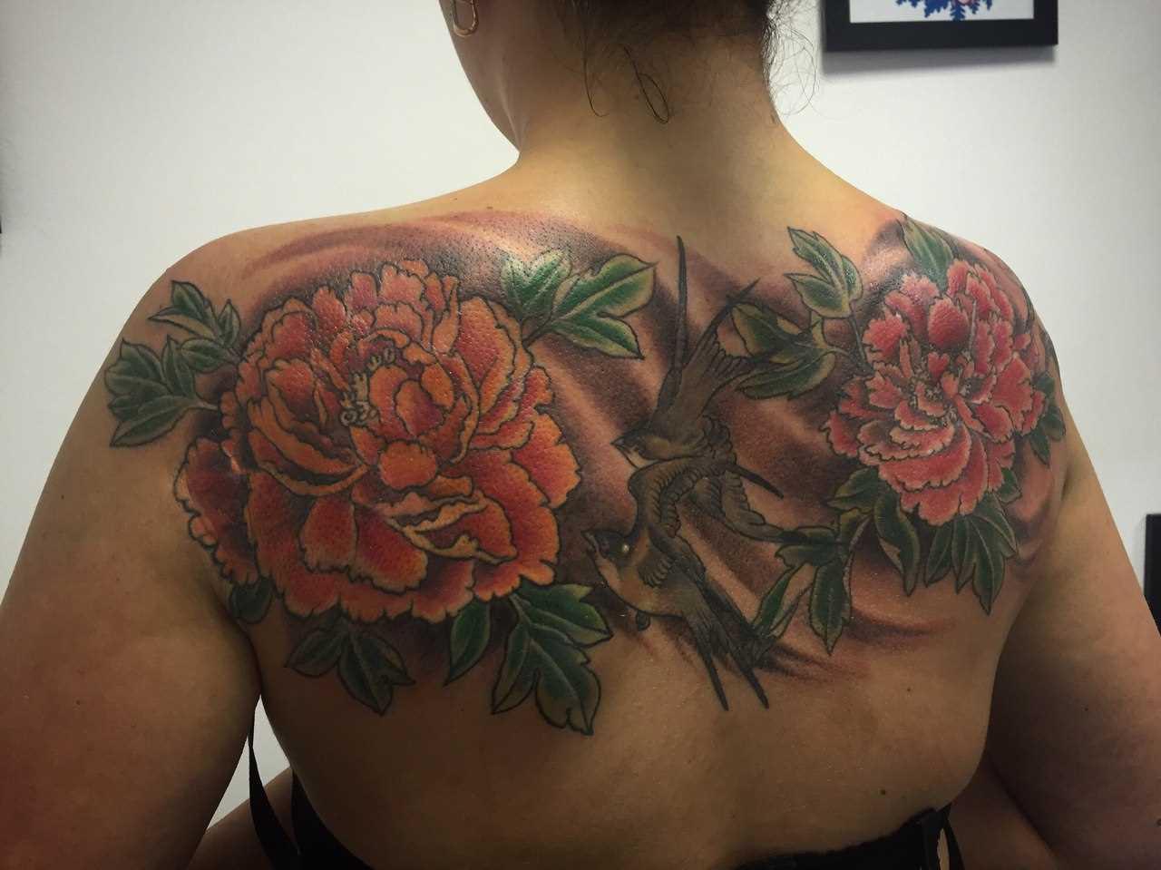 A tatuagem nas costas de uma menina - flores e andorinhas