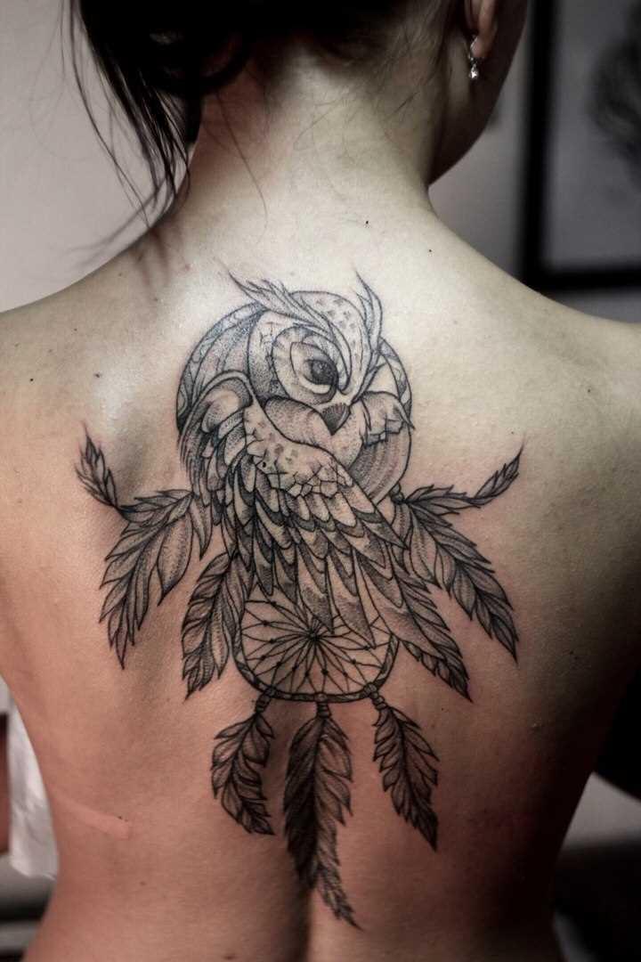 A tatuagem nas costas de uma menina - o apanhador de sonhos e coruja