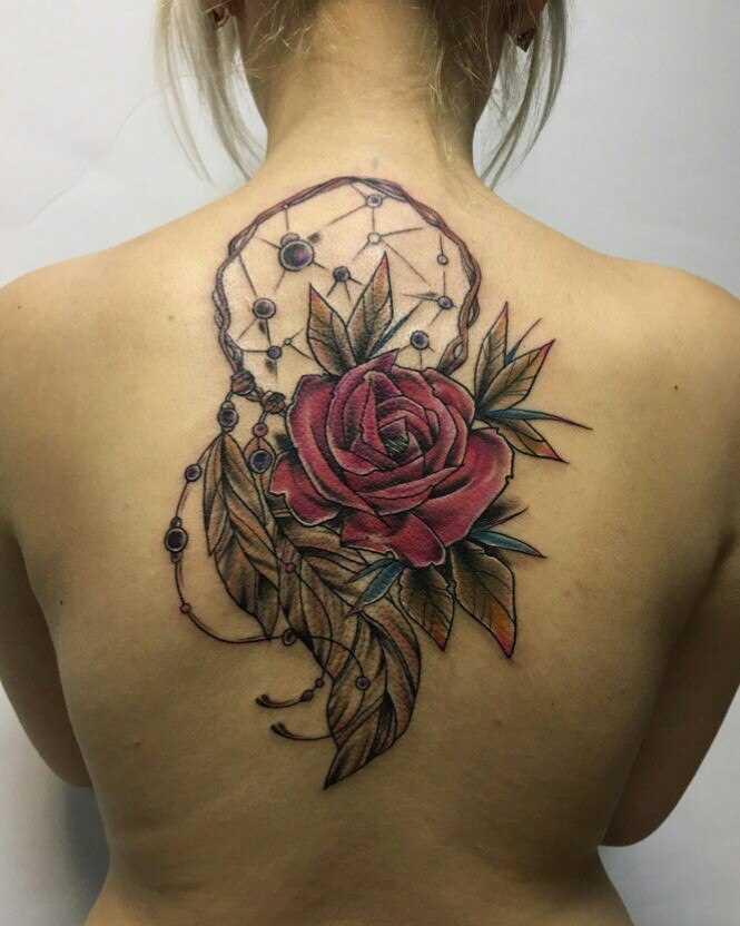 A tatuagem nas costas de uma menina - o apanhador de sonhos e rosa