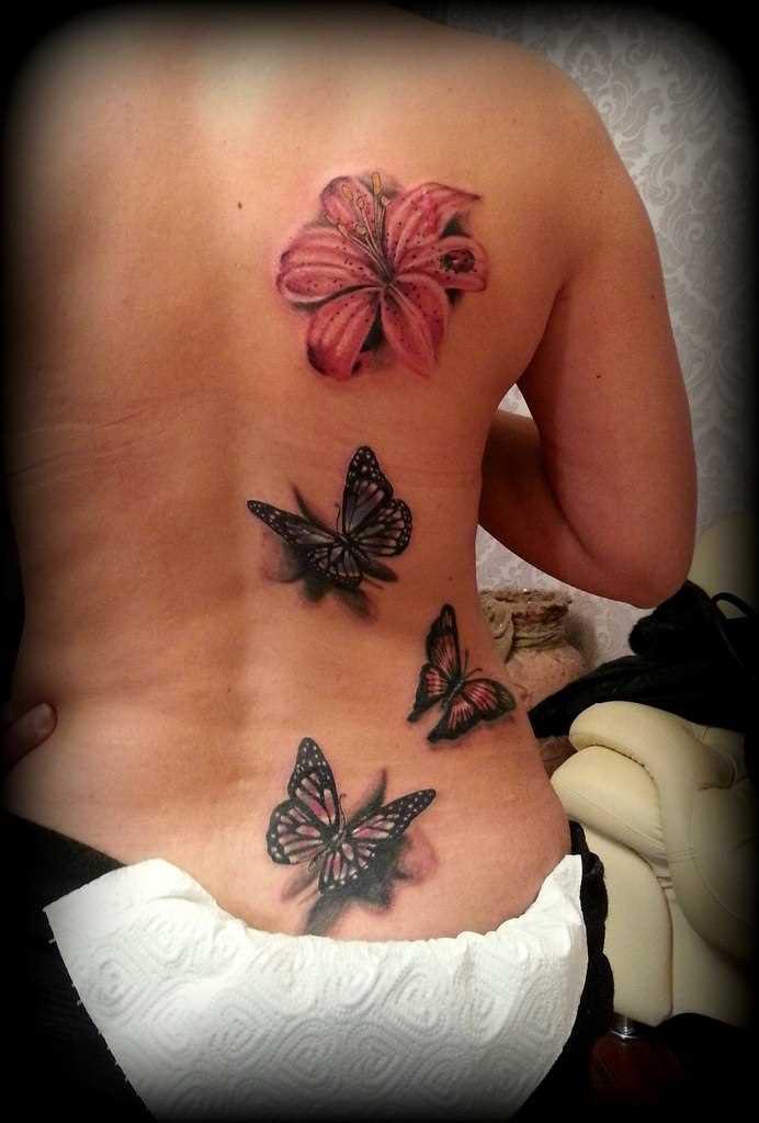 A tatuagem nas costas de uma menina - o lírio e a borboleta