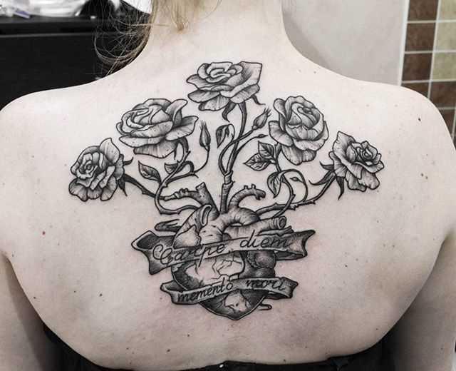 A tatuagem nas costas de uma menina - rosa e o coração