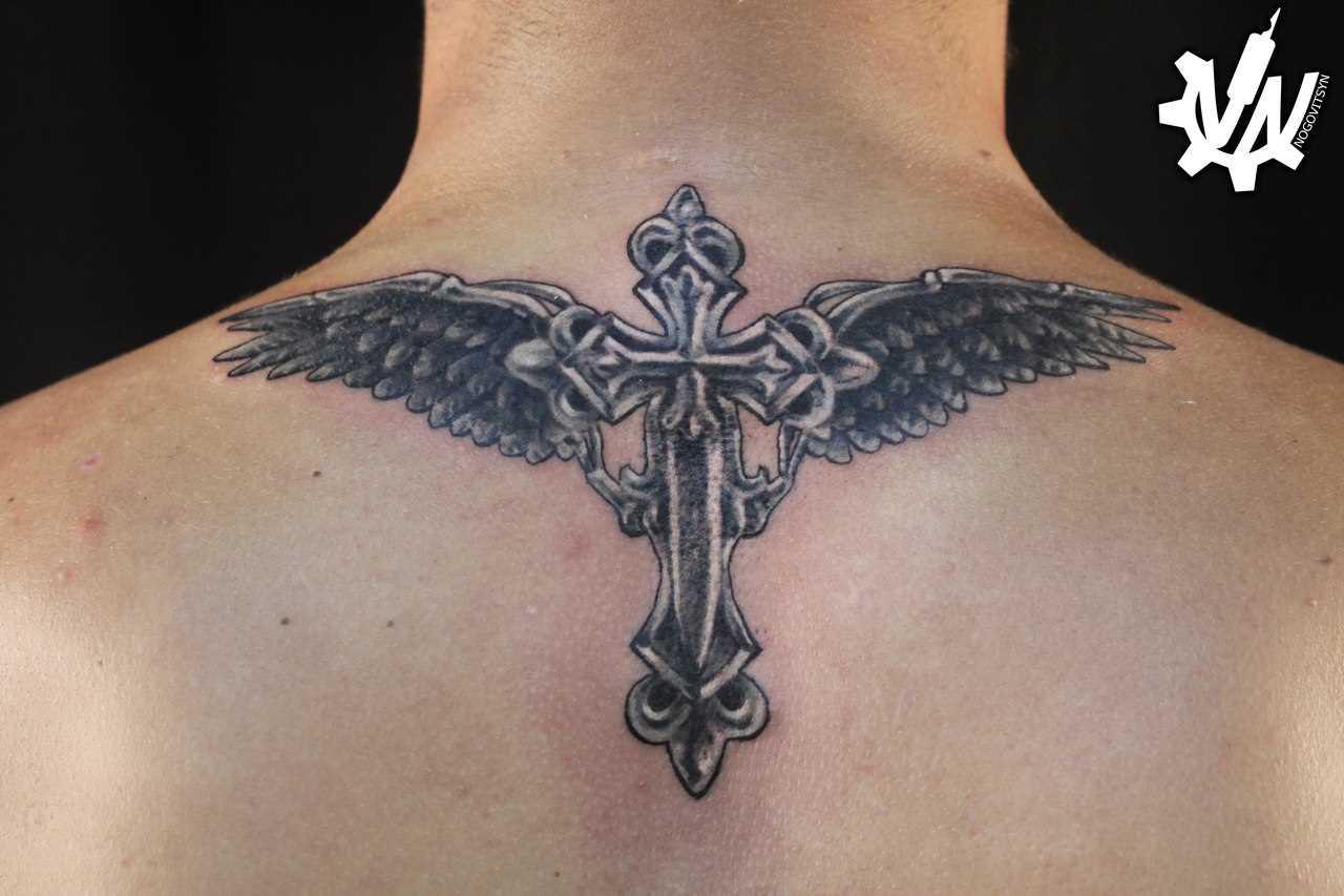 A tatuagem nas costas do cara - a cruz e asas