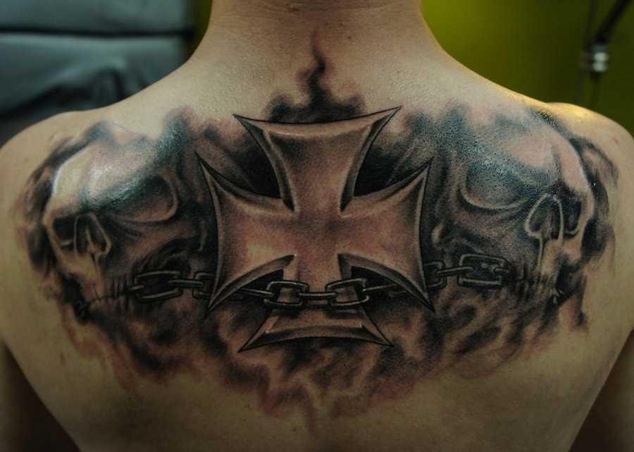 A tatuagem nas costas do cara - a cruz e o crânio
