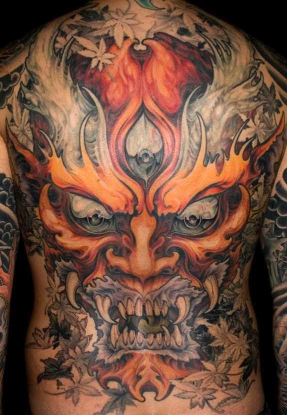 A tatuagem nas costas do cara - a grande máscara e folhas
