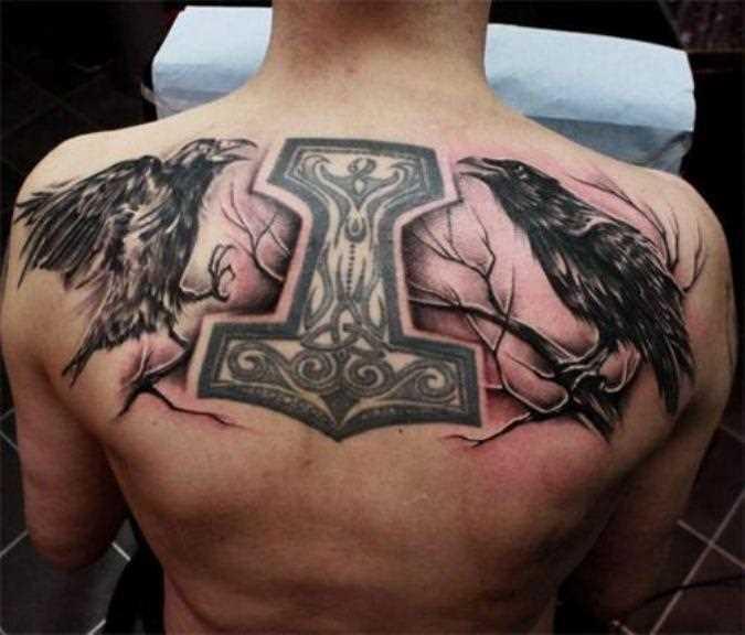 A tatuagem nas costas do cara - de-martelo e dois corvo