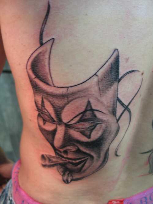 A tatuagem nas costas do cara - máscara com o cigarro