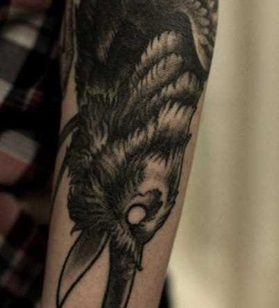 A tatuagem no braço de um cara – de- corvo