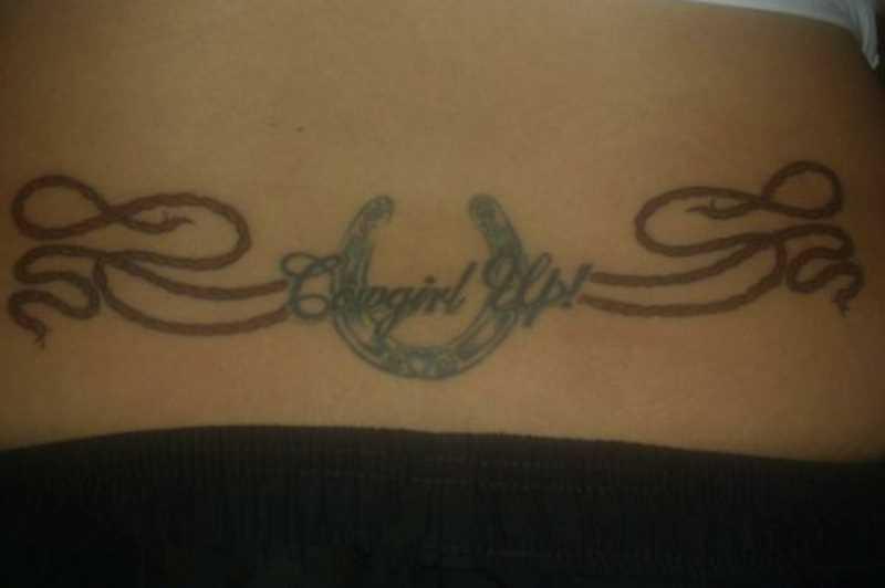 A tatuagem no cóccix meninas - ferradura, a inscrição e a corda