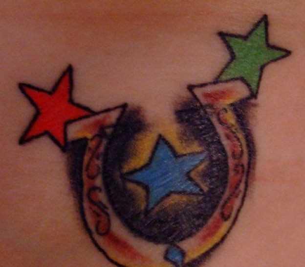 A tatuagem no cóccix meninas - ferradura e as estrelas