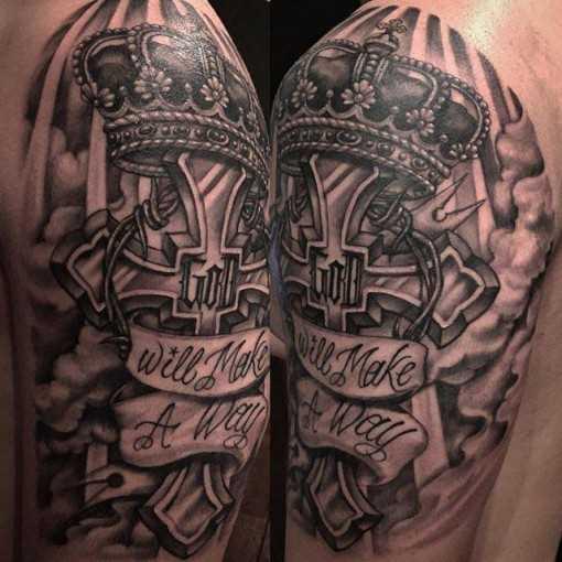 A tatuagem no estilo chicano na mão de um cara - coroa na cruz