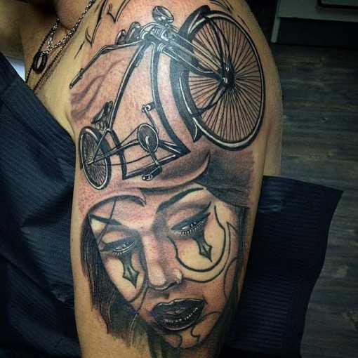 A tatuagem no estilo chicano no ombro de um cara - a bicicleta e a menina